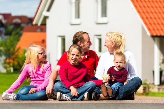 家の前に座っている幸せな家族