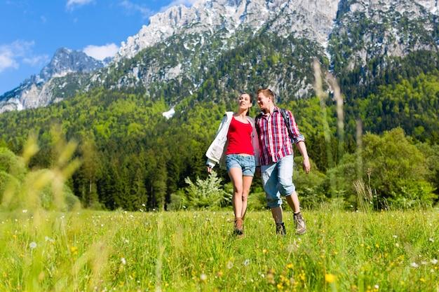 カップルは山と牧草地を歩いています。