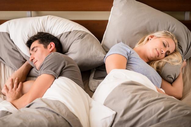 Молодой мужчина и женщина спят спиной к спине