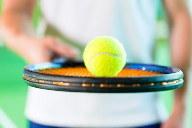 フィットネスクラブでテニスをしている女性