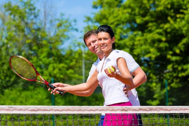 Учитель тенниса учит женщину играть