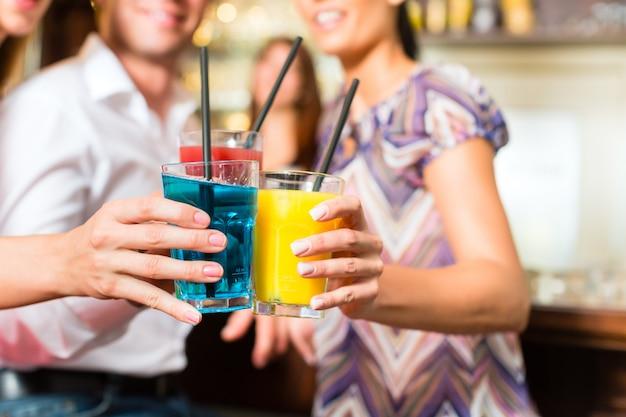 Молодые люди с коктейлями в баре