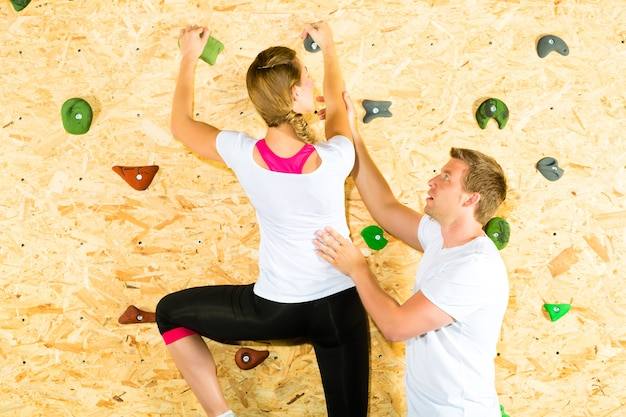 女と男がクライミングウォールで登山