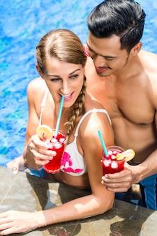 アジアのホテルプールでカクテルを飲むカップル
