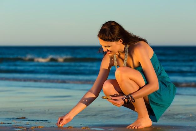 夕暮れ時の貝殻を探している女性