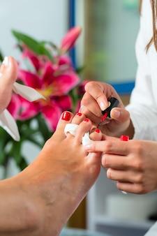 Женщина в ногтевой студии получает педикюр