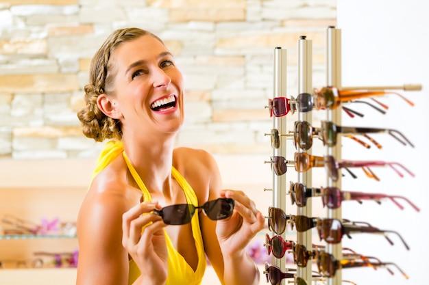 メガネのショッピングサングラスで若い女性