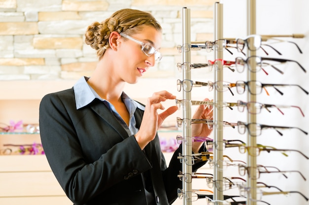 Молодая женщина в оптике с очками, она может быть клиентом или продавцом
