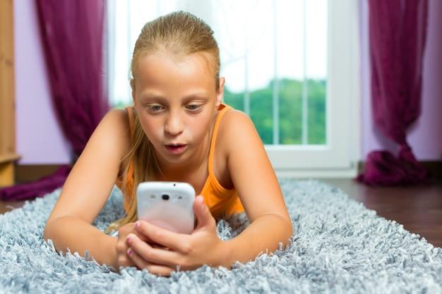 家族、携帯またはスマートフォンを持つ子供