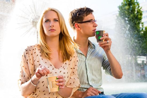 楽しんでいるカップルが休憩でコーヒーを奪う