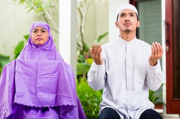 アジアのイスラム教徒のカップル、男と女、自宅で祈る
