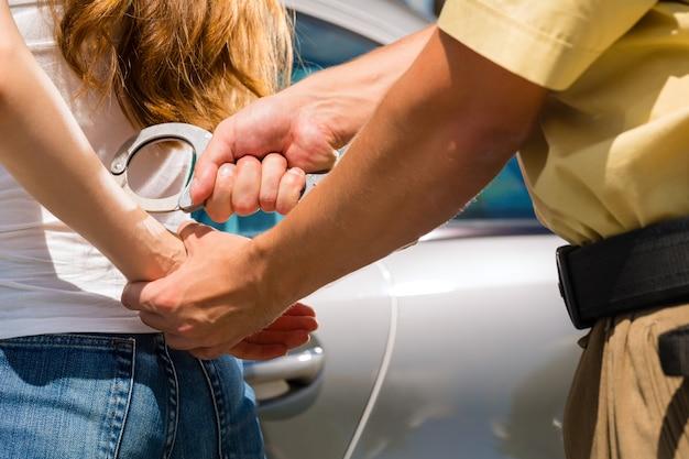 手錠で女性を逮捕する警察官
