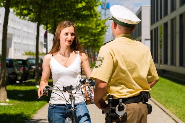 警察、警察官と自転車の女性