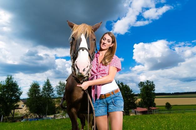 馬と牧草地の若い女性