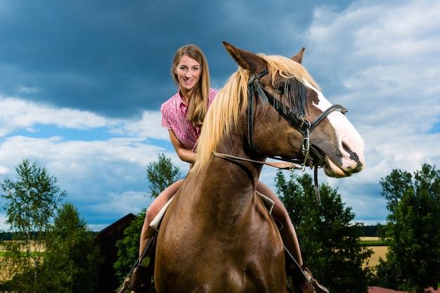 牧草地で馬に乗る若い女性