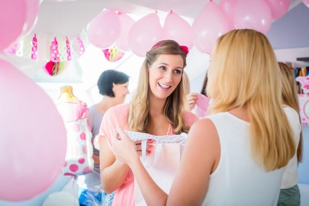 ベビーシャワーで妊娠中の友人に贈り物を与える女性