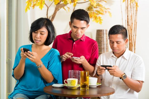 携帯電話を楽しんでいるアジアの人々