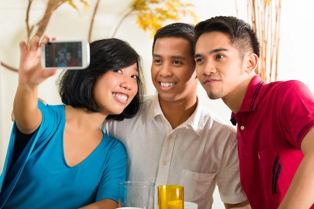 アジアの友人が携帯電話で写真を撮る