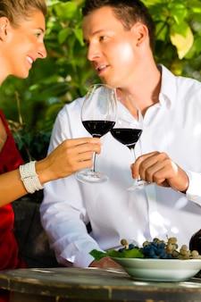 ワインを飲むブドウ園の男女