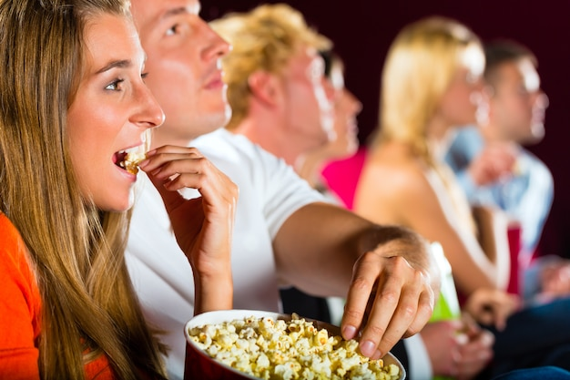 映画館で映画を見ている若者
