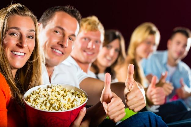 Люди смотрят кино в кинотеатре и веселятся