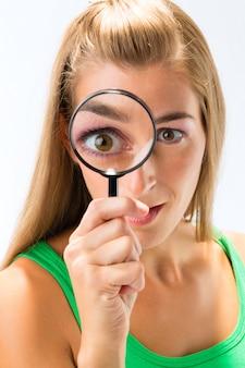 Женщина смотрит через увеличительное стекло или лупу