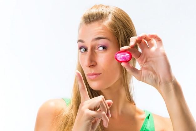 コンドームを持つ若い女性