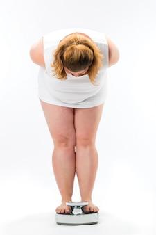 スケールに立っている肥満の若い女性