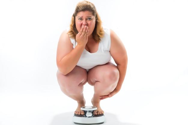スケールで身をかがめる肥満の若い女性