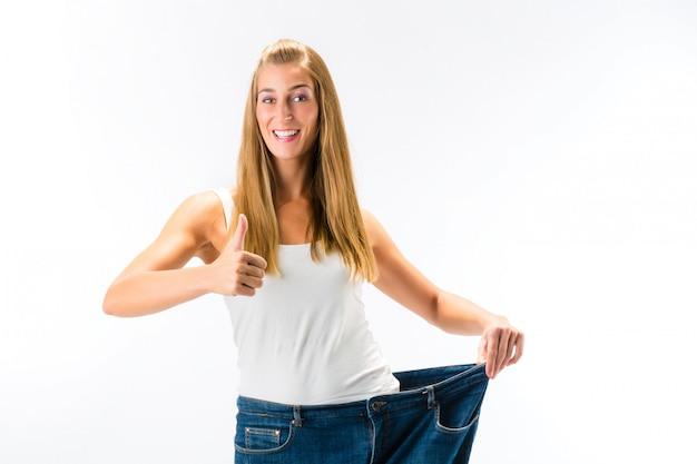 重量を失った後立っていると大きすぎるズボンを着ている女性