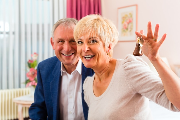 Пожилые супружеские пары, сидя на кровати в гостиничном номере