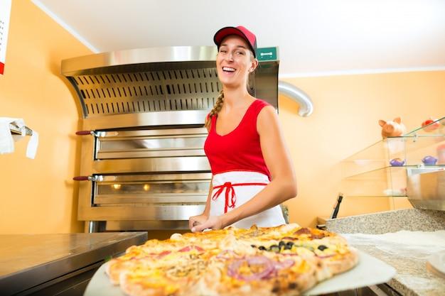 完成したピザをオーブンから押す女性