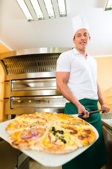 完成したピザをオーブンから押す男