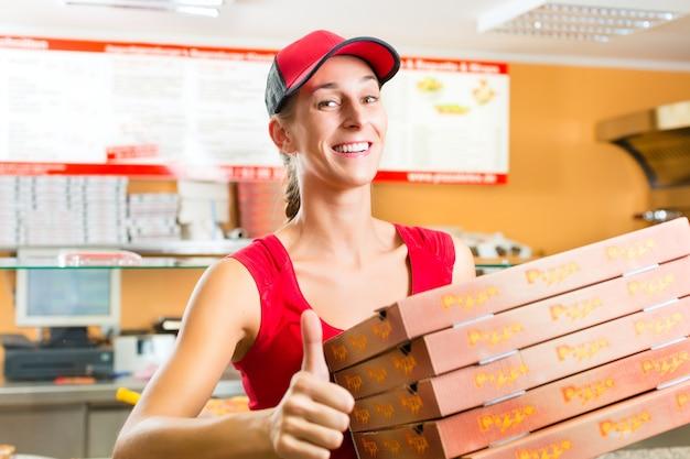 配達サービス、ピザの箱を保持している女性