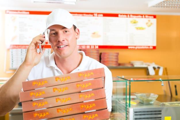 宅配サービス、ピザの箱を持って男