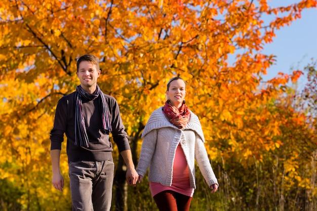 秋にカラフルな木の前で散歩を持っているカップル