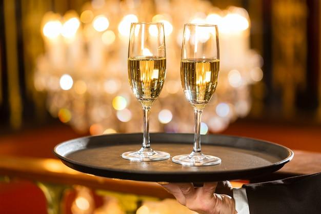 高級ダイニングレストランのトレイでシャンパングラスを提供するウェイター、大きなシャンデリアが