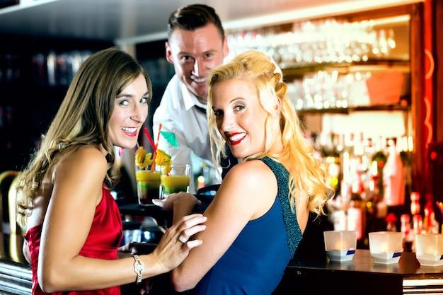 Молодые женщины в баре или клубе, бармену подают коктейли