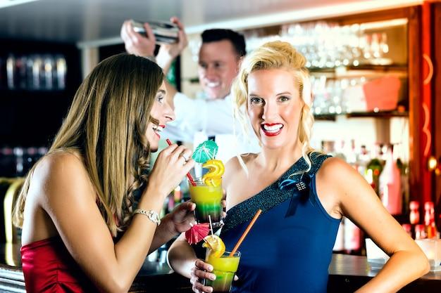 バーやクラブでカクテルを持つ若い女性、バーテンダーは飲み物を混合しています