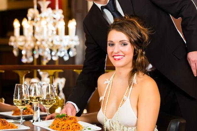 高級ダイニングレストランのテーブルに座っているきれいな女性、ウェイターが夕食を提供、大きなシャンデリアが