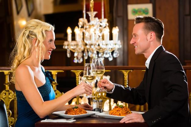 У счастливой пары романтическое свидание, ресторан изысканной кухни, они пьют вино и чокаются, ура, большая люстра