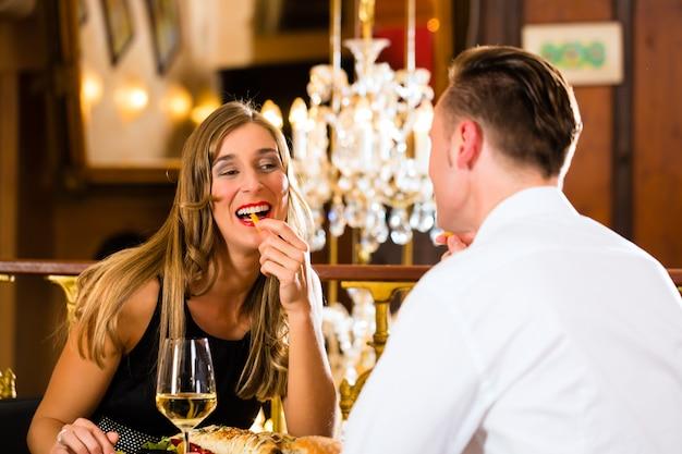 カップル、男性と女性、ファーストフードとフライドポテトを食べる高級レストラン