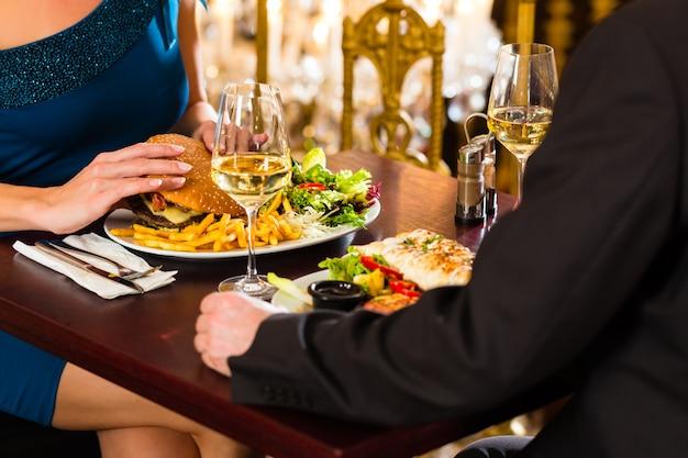カップル、男性と女性、ファーストフード、ハンバーガー、フライドポテトを食べる高級レストラン