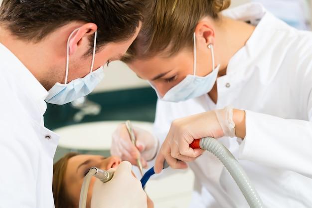 マスクと手袋を着用して歯科医と助手歯科治療の女性患者