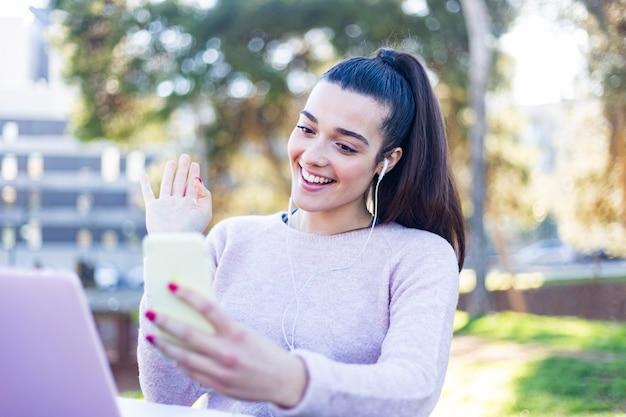 Молодая красивая женщина с хвостиком, используя смартфон на открытом воздухе, чтобы сделать видео-конференцию