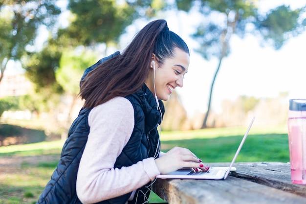 Красивая молодая женщина на линии просмотра социальных медиа с ноутбуком