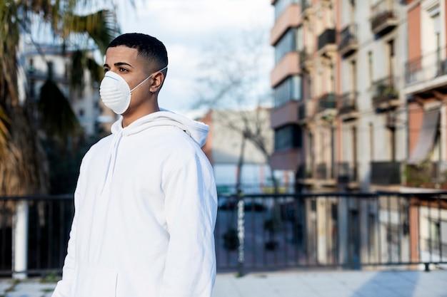 伝染性感染症に対する、また公共の場でのインフルエンザやコロナウイルスに対する保護としての防護マスクを身に着けている若い男性の側面図。