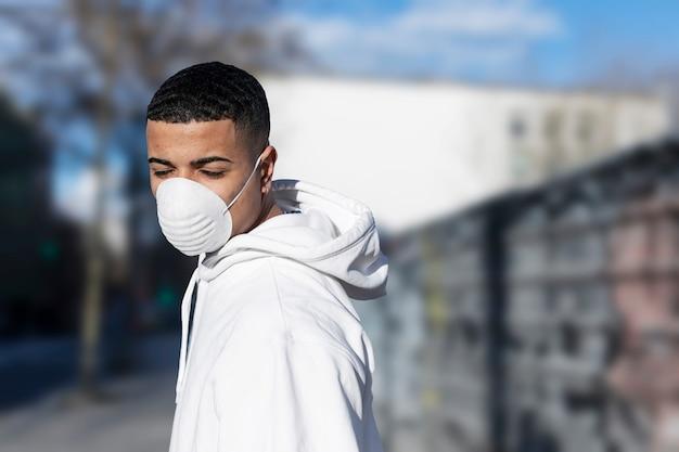 Закройте вверх по портрету молодого мужчины нося защитную лицевую маску против заразных инфекционных заболеваний и как защита от гриппа или коронавируса в общественном месте.