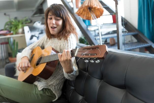 Красота женщины, сидящей на дофе и играющей на гитаре