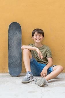 一人で座っているスケートボードと微笑む少年